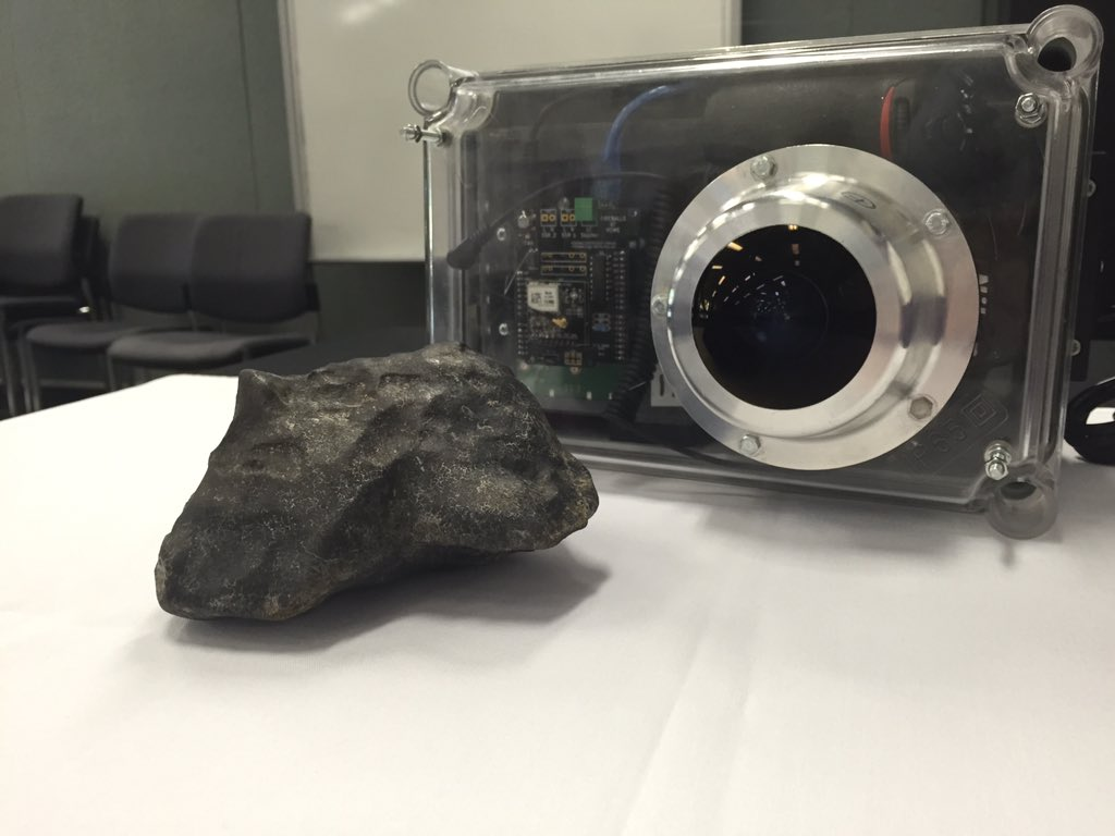 Cleaned meteorite next to a DFN camera at the press conference on January 6, 2016 / image credit: Ryan Emery SBS